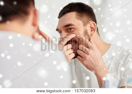 beauty, hygiene, skin problem and people concept - smiling young man looking to mirror and squeezing pimple at home bathroom over snow