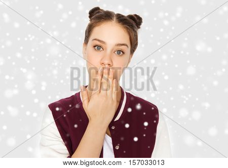 winter, christmas, people, expression and teens concept - confused teenage girl covering her mouth by hand over gray background and snow