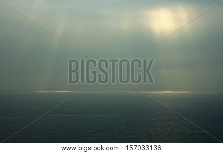 Sea horizon with ripples against grey sky at dusk bleakness over seascape background