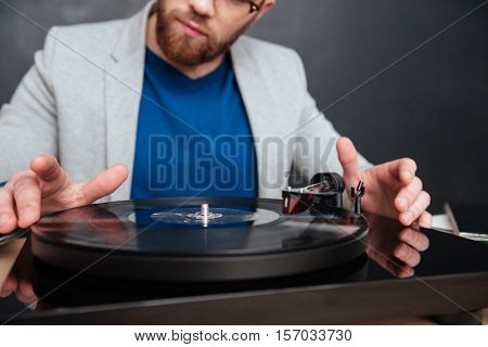 Closeup of turntable used by concentrated bearded man