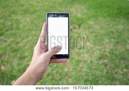Man's left hand hold blank white screen mobile phone with blurry scene of green grass in park.