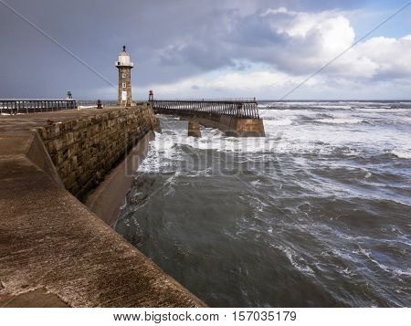 WHITBY ENGLAND - NOVEMBER 5: East Lighthouse and rough sea. In Whitby North Yorkshire England. On 5th November 2016.