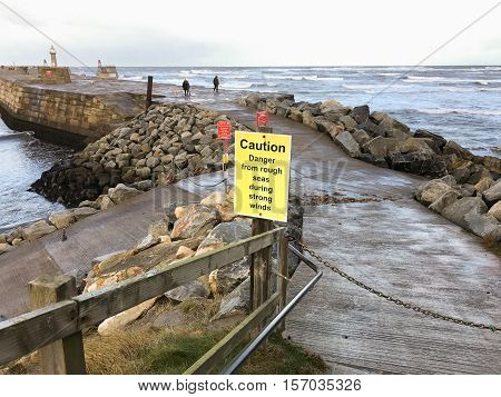 WHITBY ENGLAND - NOVEMBER 5: Sign warning of rough seas on East Pier. In Whitby North Yorkshire England. On 5th November 2016.