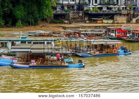 YANGSHUO CHINA - JUNE 12: Bamboo rafts and boats in port on Li river in Yangshuo Guilin China. Boat and raft cruises are one of the most popular tourist attractions in region. June 2016