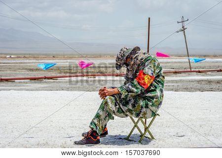 Guard Sleeping On The Chair At Chaqia Lake, China