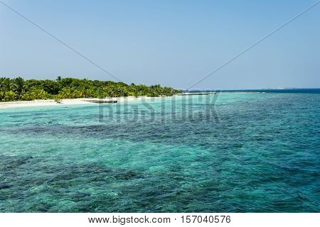 Daylight scene shot in the Maldives showing the amazing turquoise color of the indian ocean, white sand beach, blue sky without clouds and some palms, scene appearing to invite everyone to visit Maldives or to go on holiday.