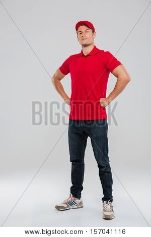 Full length portrait of deliveryman. arms akimbo. looking at camera. in studio. isolated gray background