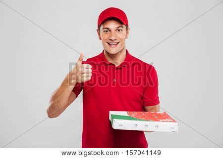 Smiling pizza delivery man in studio. looking at camera. isolated gray background