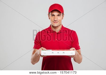 Pizza deliveryman in studio. front view. looking at camera. isolated gray background