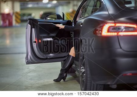 Rear view of modern car with open driver door and leg and arm of woman comes out.