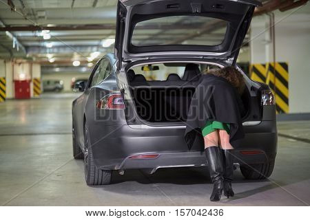 Young woman rummages in trunk of car standing at underground parking, rear view.