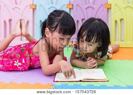 Asian Chinese Little Sisters Laying On The Floor Reading