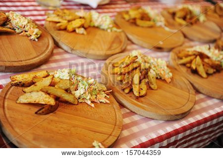 Baked Potato Wedges with salad on wood desk