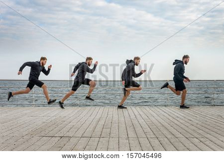 Four men clones running in sports wear along seaside on a wooden surface