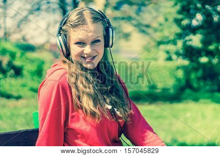 Young lady listening to music and relaxing on a park bench - retro style