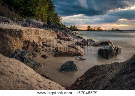 The coastline of sand and stones on a background of clouds evening light