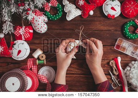 felt Christmas decorations on the wooden table - woman is preparing for handmade