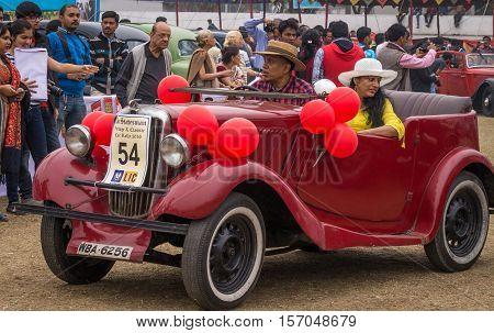 KOLKATA, INDIA - JANUARY 31, 2016: An aged couple drives their Austin vintage car after flag off at the Statesman Vintage Car Rally at Fort William Kolkata.