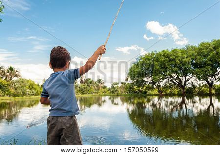 Kid fishing on a lake. Little boy learning how to fish.