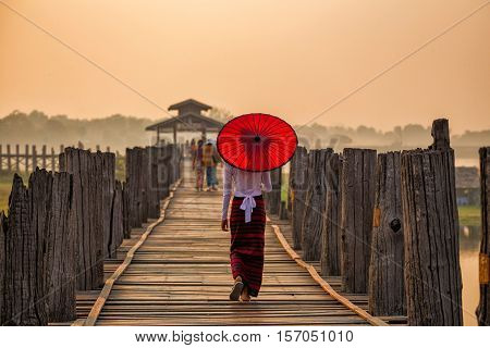 Burmese girl holding a red umbrella walking on U Bein Bridge in the morning in Mandalay Myanmar.