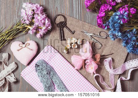 Sewing set of different decorative elements for handicraft and items for handmade on wooden background