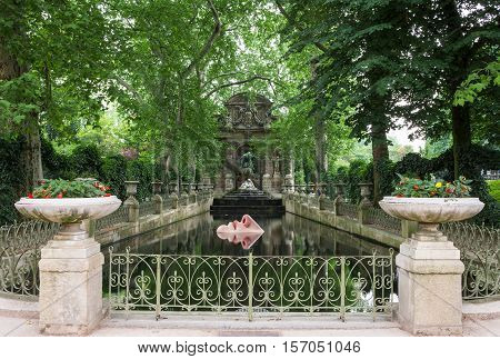Paris France - June 27 2006: A closeup of the Fontaine de Medicis with a modern installation of floating mobile of a face by Lotta Hannerz
