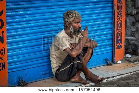 KOLKATA, INDIA - OCTOBER 8, 2016: Old Indian male beggar sits in front of a closed shop and has a cup of morning tea on a road in South Kolkata, West Bengal, India.