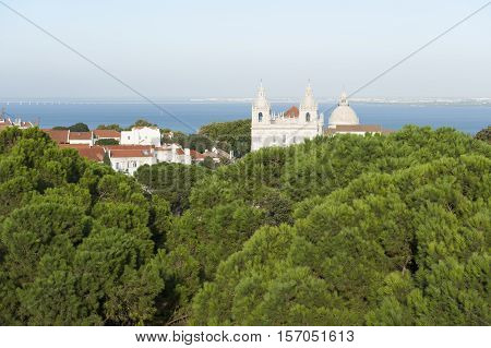 View of the Tagus river in Lisbon with church over trees