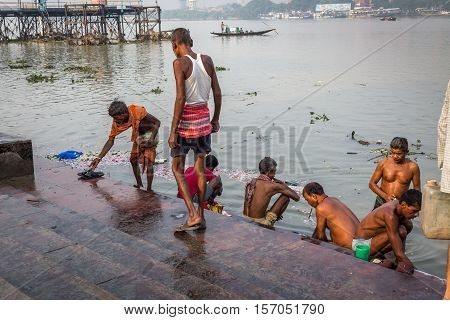 KOLKATA, INDIA - OCTOBER 8, 2016: People taking a bath at Mallick ghat near Howrah bridge before starting their daily scores. This ghat is well known for the popular flower market of Kolkata.