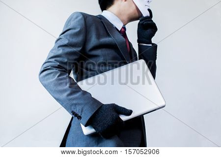 Business man in white mask wearing gloves and stealing computer and digital information - fraud hacker theft cyber crime concept