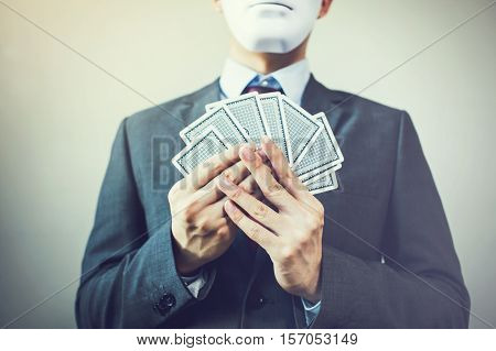 Businessman in mask holding a set of cards - hiding expression in business strategic competition concept.