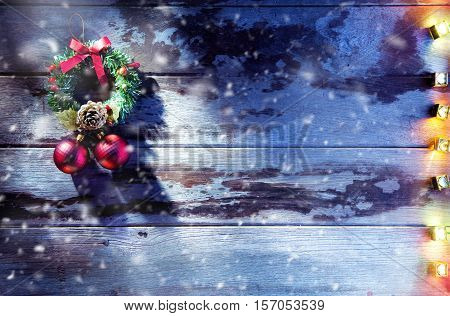 close up view of christmas wreath and lights on wooden back