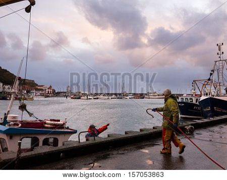 SCARBOROUGH ENGLAND - NOVEMBER 5: Dock workers fuelling fishing boat Scarborough harbour. In Scarborough England. On 5th November 2016.