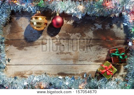 close up view of christmas tree toys, gifts  and lights on wooden back