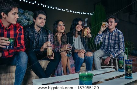 Happy young friends laughing and talking while woman showing beer at camera in a outdoors party. Friendship and celebrations concept.
