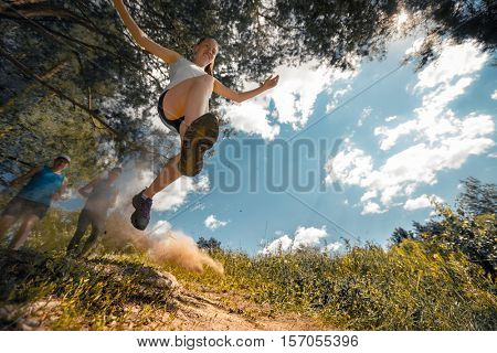 Trail running athlete jumping over camera at sunny day