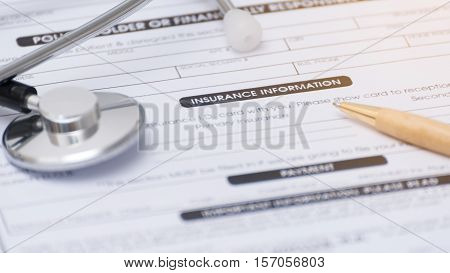 Close-up of health insurance formStethoscope and pen on a health insurance application medical information
