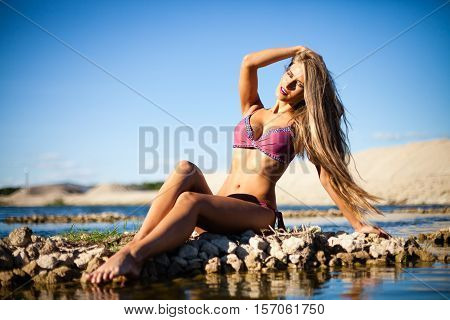 Caucasian long hair model posing in bikini.