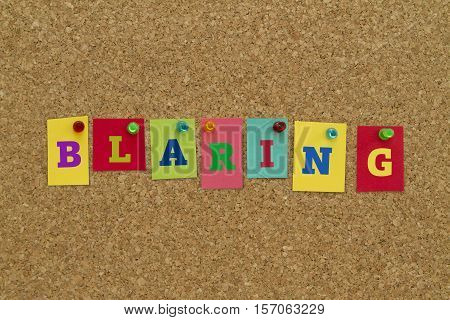 Blaring word written on colorful sticky notes pinned on cork board.