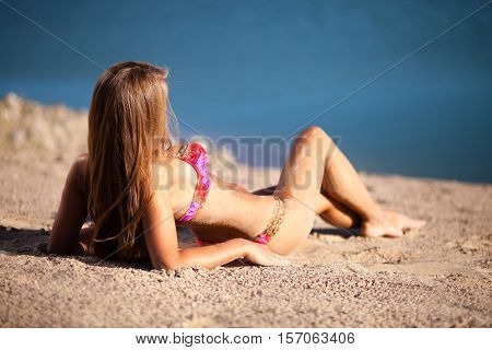 Long hair girl in bikini on beach.