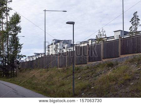 Noise protection wall, barrier along a European highway. Modern suburban settlement in the background. Footway this side.