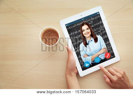 Woman video conferencing with tutor on tablet at home. Distance education concept.