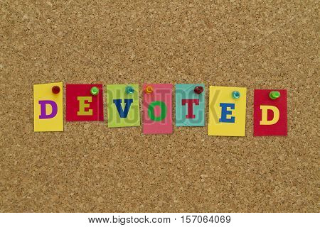 Devoted word written on colorful sticky notes pinned on cork board.