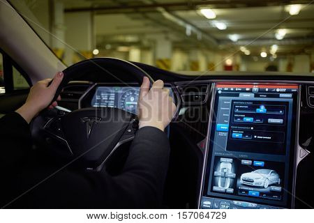 MOSCOW, RUSSIA - NOV 11, 2015: Woman drives Tesla Mosel S car in underground parking. The Tesla Model S produced by Tesla Motors, and introduced in June 2012.