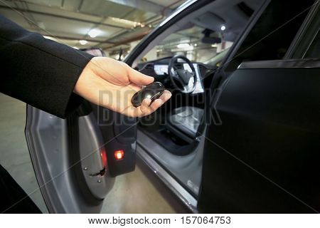 MOSCOW, RUSSIA - NOV 11, 2015: Female hand with remote control of the Tesla Model S car. The Tesla Model S produced by Tesla Motors, and introduced in June 2012.