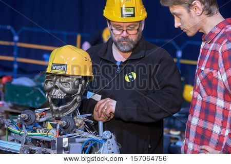 MOSCOW, RUSSIA - FEB 22 2016: Engineers prepare rope climber robot Skelly during International Championship Bronebot at Olympic stadium. Bronebot inscriptions on protective helmets.
