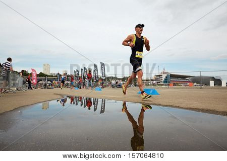 MOSCOW, RUSSIA - AUG 14, 2016: Participants of cross-country stage of traditional 3Grom series triathlon contest at Krylatskoye Rowing Channel sports complex.