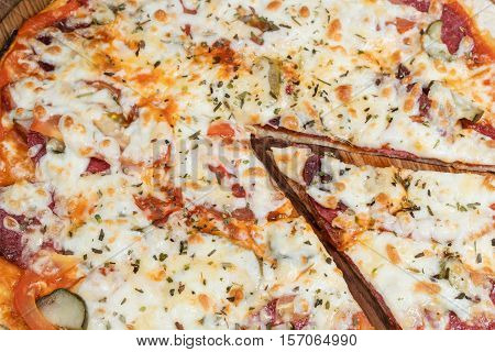 Delicious round pizza with salami and pickles with cut off piece closeup