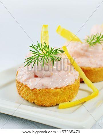 Taramasalata canape fish-roe spread bites with lemon slices on white tray Shallow dof.