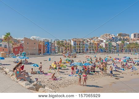 La Vila Joiosa, Spain - August 25, 2016: Colorful homes and buildings form backdrop to busy summer Mediterranean beach crowded with people and sun umbrellas